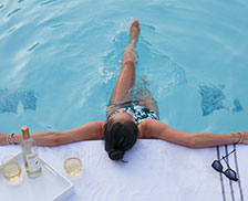 SENZA Hotel Dining - Woman enjoying wine and relaxing in pool